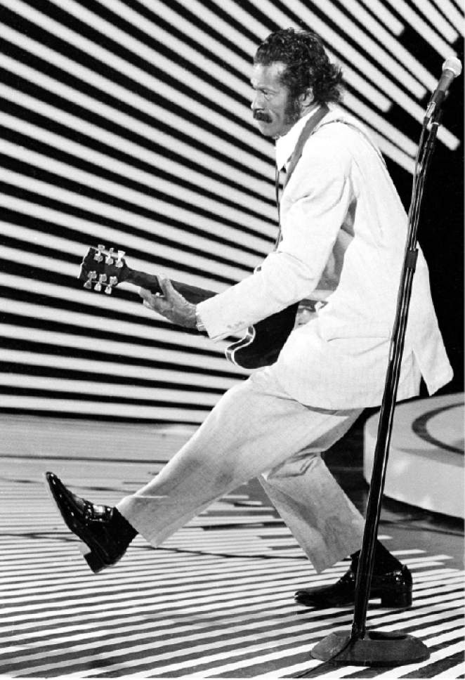 """FILE - In this April 4, 1980 file photo, guitarist and singer Chuck Berry performs his """"duck walk"""" as he plays his guitar on stage. On Saturday, March 18, 2017, police in Missouri said Berry has died at the age of 90. (AP Photo)"""