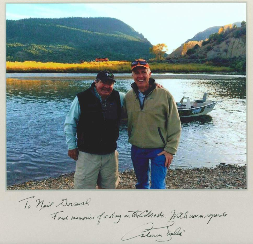 """This photo provided by the Gorsuch family shows Judge Neil Gorsuch posing with Supreme Court Justice Antonin Scalia that he autographed. Gorsuch is roundly described by colleagues and friends as a silver-haired combination of wicked smarts, down-to-earth modesty, disarming warmth and careful deliberation. His critics largely agree with that view of the self-described """"workaday judge"""" in polyester robes. Even so, they're not sure it's enough to warrant giving him a spot on the court.  (Glenn Summers/Gorsuch family via AP)"""