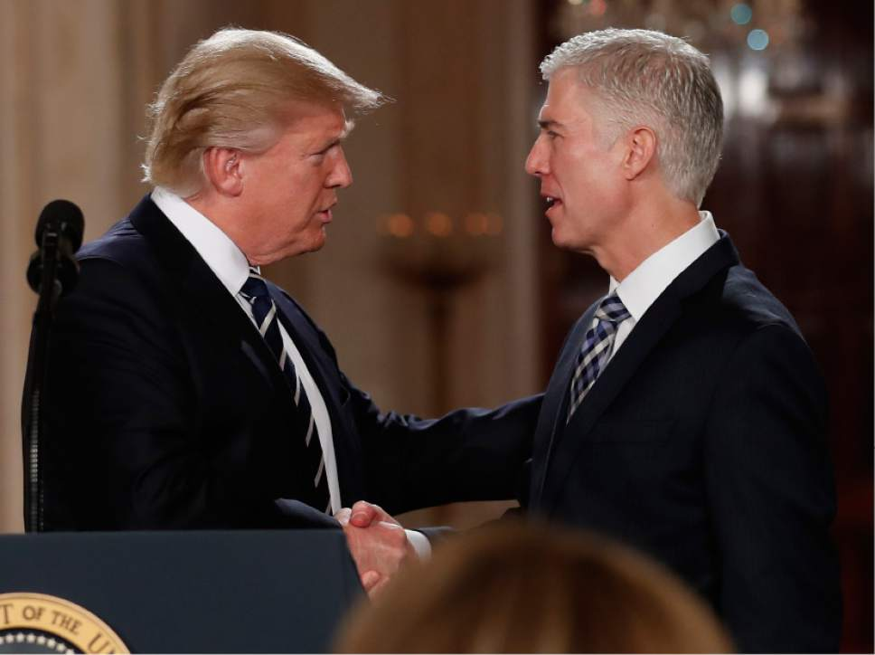 """FILE - In this Jan. 31, 2017, file photo, President Donald Trump shakes hands with 10th U.S. Circuit Court of Appeals Judge Neil Gorsuch, his choice for Supreme Court Justice in the East Room of the White House in Washington.  Gorsuch is roundly described by colleagues and friends as a silver-haired combination of wicked smarts, down-to-earth modesty, disarming warmth and careful deliberation. His critics largely agree with that view of the self-described """"workaday judge"""" in polyester robes. Even so, they're not sure it's enough to warrant giving him a spot on the court. (AP Photo/Carolyn Kaster, file)"""
