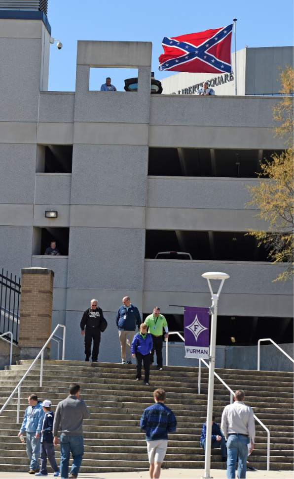 Basketball fans walk past as a Confederate flag flies from a parking deck outside the arena before a second-round game of the NCAA men's college basketball tournament in Greenville, S.C., Sunday, March 19, 2017. A small group of protesters flew a large Confederate flag from the top of a parking garage next to the arena hosting two men's NCAA Tournament games. (AP Photo/Rainier Ehrhardt)