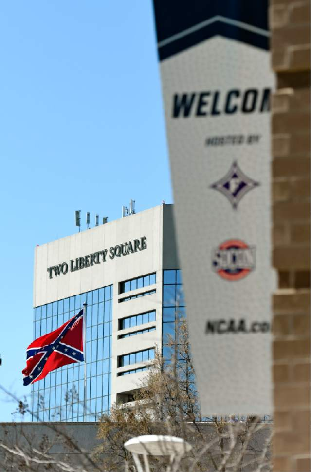 A Confederate flag flies from a parking deck outside the arena before a second-round game of the NCAA men's college basketball tournament in Greenville, S.C., Sunday, March 19, 2017. A small group of protesters flew a large Confederate flag from the top of a parking garage next to the arena hosting two men's NCAA Tournament games. (AP Photo/Rainier Ehrhardt)