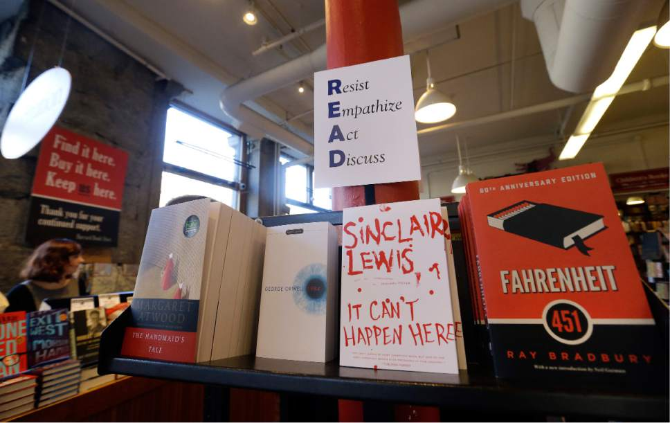 "Books are displayed under a sign at the Harvard Book Store, Thursday, March 9, 2017, in Cambridge, Mass. Readers have been flocking to classic works of dystopian fiction in the first months of Donald Trump's presidency. Novels depicting dysfunctional societies have shot to the top of best-seller lists in recent months, including George Orwell's ""1984"" and Margaret Atwood's ""The Handmaid's Tale."" Publishers credit Trump's election for sparking demand. (AP Photo/Elise Amendola)"