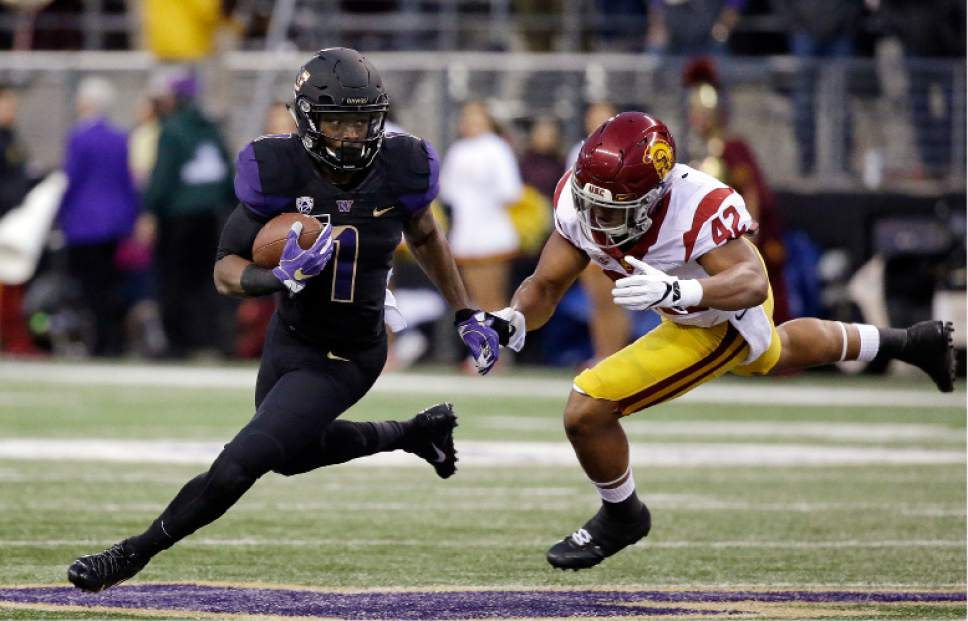 Washington's John Ross, left, runs with the ball as Southern California's Uchenna Nwosu chases him in the first half of an NCAA college football game Saturday, Nov. 12, 2016, in Seattle. (AP Photo/Elaine Thompson)