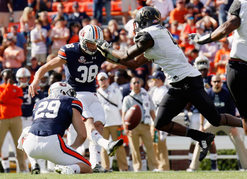 FILE - In this Nov. 5, 2016, file photo, Vanderbilt's Zach Cunningham, right, blocks a field goal attempt of Auburn's Daniel Carlson after he hurdled the line of scrimmage in the second half of an NCAA college football game in Auburn, Ala. The NCAA rules committee has proposed making hurdling over linemen to block a kick illegal and expanding what constitutes a horse-collar tackle. It decided against tinkering with the targeting rule to eliminate the ejection penalty for some of the fouls.  (Todd J. Van Emst/Opelika-Auburn News via AP, File)