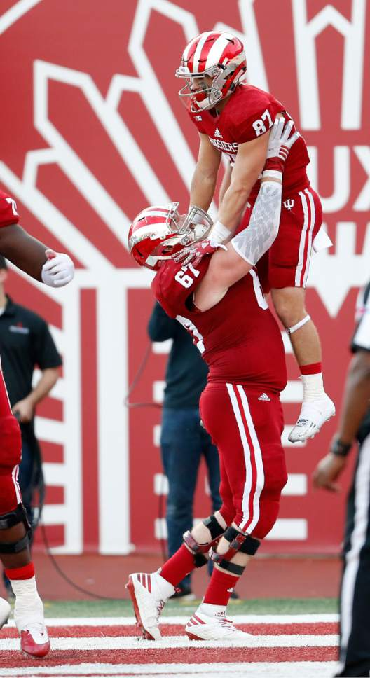 FILE - In this Oct. 29, 2016, file photo, Indiana offensive lineman Dan Feeney (67) lifts teammate wide receiver Mitchell Paige (87) after his touchdown against Maryland during the second half of an NCAA college football game in Bloomington, Ind. Feeney was selected to the 2016 AP All-America college football team, Monday, Dec. 12, 2016.  (AP Photo/Sam Riche, File)