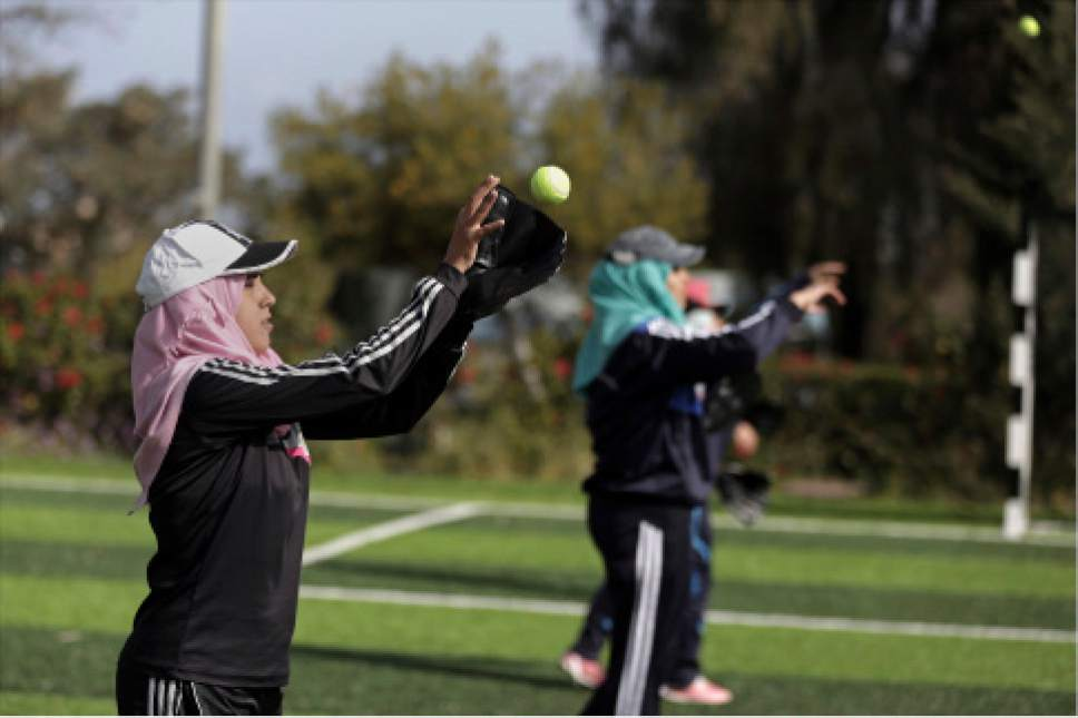 In this Sunday, March 19, 2017 photo, Palestinian women practice with tennis balls while training for an all women's baseball game, on a soccer field in Khan Younis, southern Gaza Strip. The female players wear hijabs, not helmets, toss around tennis balls, not baseballs and their leather gloves have been replaced by black imitations knitted from fabric. The group of young women are trying to bring baseball to Gaza -- giving the traditional American pastime a distinctly local feel. (AP Photo/Khalil Hamra)