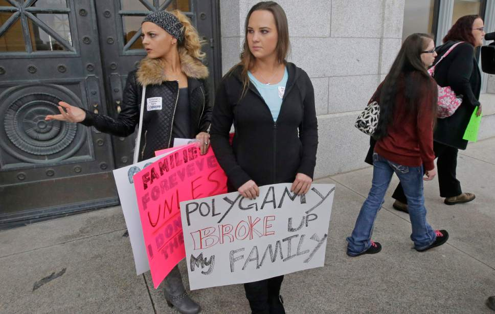 Ariel Barlow, right center, carries a sign following a news conference with former polygamists speaking in favor of Republican Rep. Mike Noel bigamy offense amendments Friday, Feb. 10, 2017, at the Utah State Capitol, in Salt Lake City. (AP Photo/Rick Bowmer)