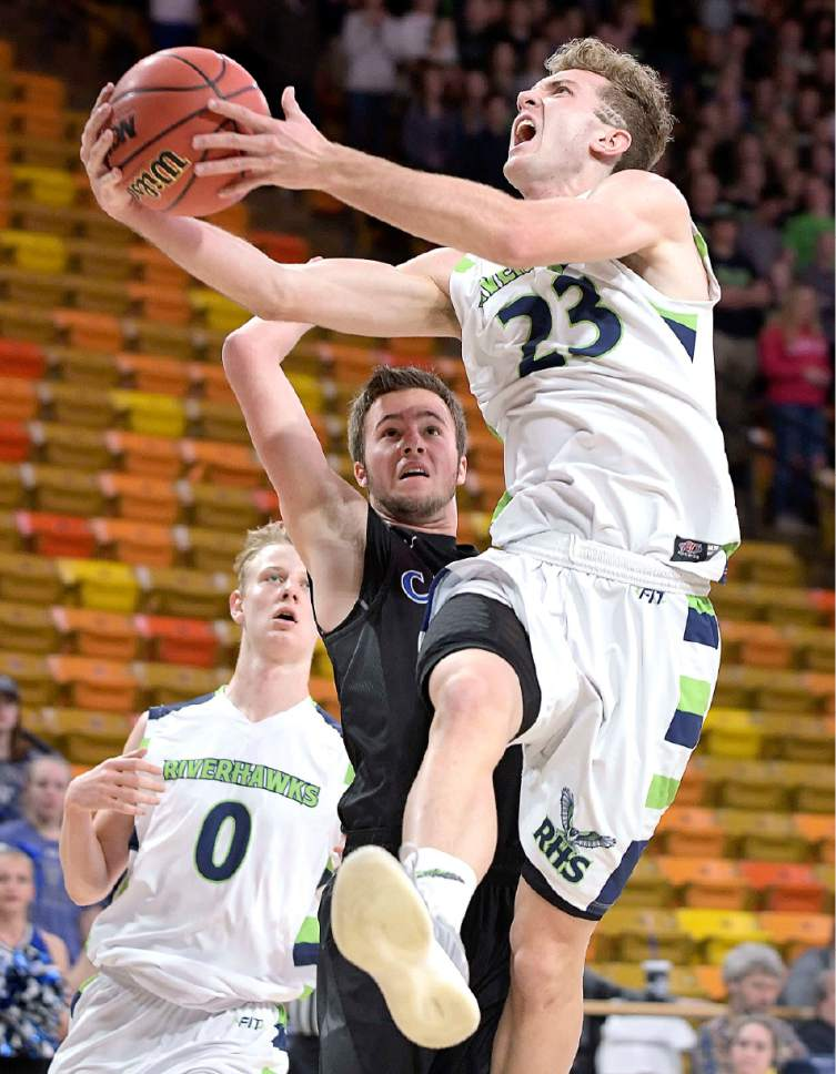 Ridgeline's Jaxon Brenchley (23) drives to the basket as Carbon's Jamin Jensen defends during their quarterfinal game in the 3A state basketball tournament on Thursday in Logan. (Eli Lucero/Herald Journal)
