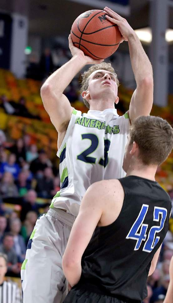 Ridgeline's Jaxon Brenchley (23) takes a shot as Carbon's Kyle Quinton (42) defends during their quarterfinal game in the 3A state basketball tournament on Thursday in Logan.  (Eli Lucero/Herald Journal)