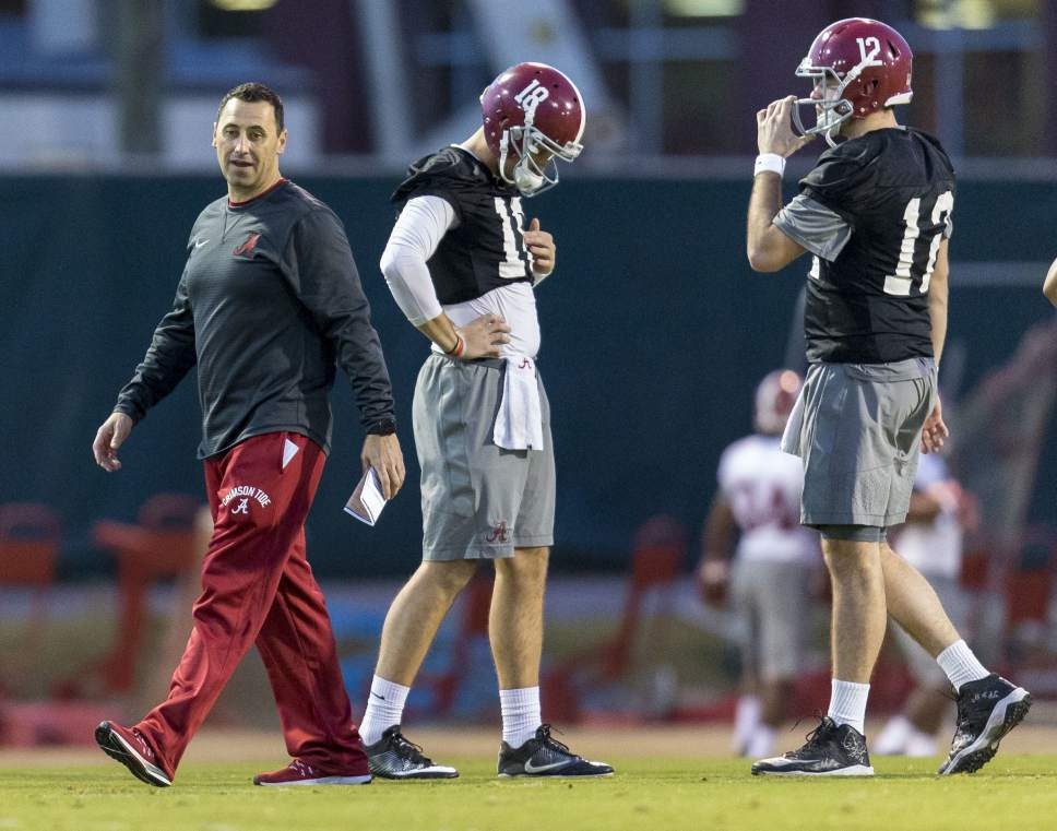 Alabama offensive coordinator Steve Sarkisian works with his players, including quarterbacks Cooper Bateman (18) and David Cornwell (12) during football practice, Tuesday, Jan. 3, 2017, at the Thomas-Drew Practice Fields in Tuscaloosa, Ala. (Vasha Hunt/AL.com via AP)