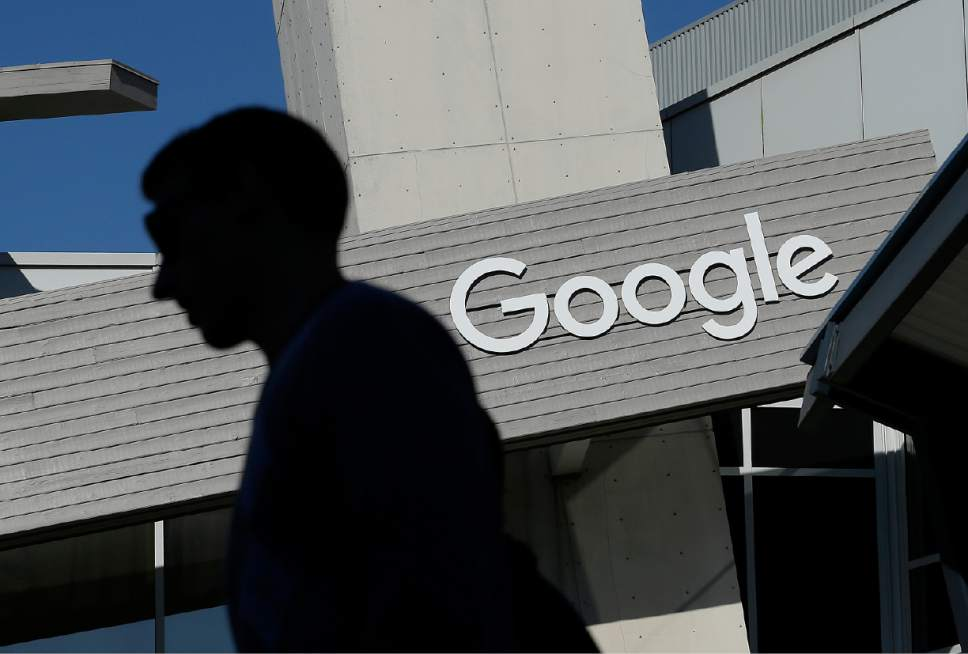 FILE - In this Nov. 12, 2015, file photo, a man walks past a building on the Google campus in Mountain View, Calif. Google is enabling users of its digital mapping service to allow their movements to be tracked by friends and family in the latest test of how much privacy people are willing to sacrifice in an era of rampant sharing. The location-monitoring feature will begin rolling out Wednesday, March 22, 2017, in an update to the Google Maps mobile app that's already on most of the world's smartphones. It will also be available on personal computers. (AP Photo/Jeff Chiu, File)