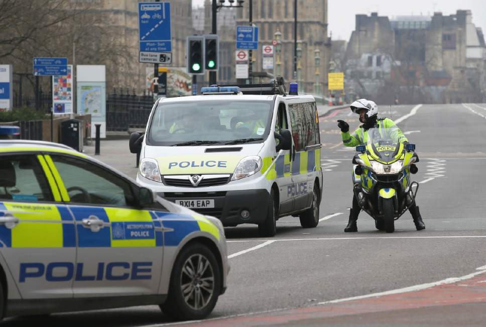 "Police officers speak as they prepare to reopen Westminster Bridge Thursday, March 23, 2017, following an attack on Wednesday when a man drove a car into pedestrians then stabbed a police officer to death before being fatally shot by police within Parliament's grounds. The IS-linked Aamaq news agency said Thursday that the person who carried out the ""attack in front of the British parliament in London was a soldier of the Islamic State."" (AP Photo/Tim Ireland)"