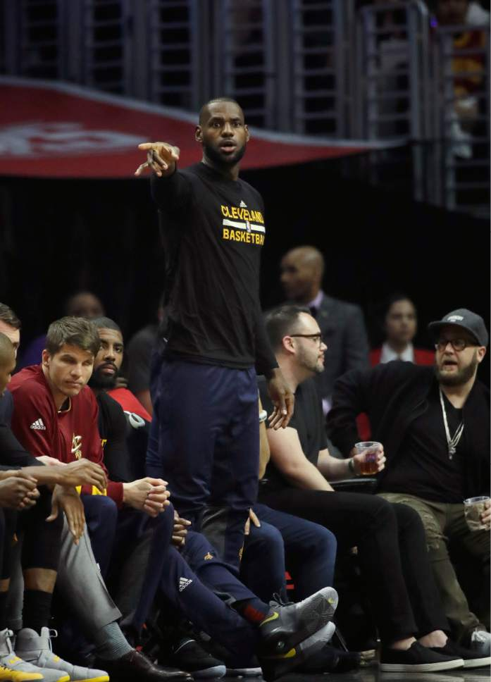 0854d9be095b Cleveland Cavaliers  LeBron James watches from the bench during the first  half of an NBA