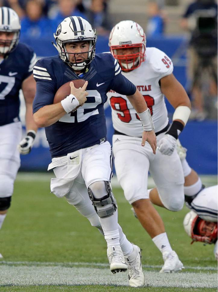 FILE - This Nov. 12, 2016, file photo, shows BYU quarterback Tanner Mangum, left, carrying the ball as he is pursued by Southern Utah defensive lineman Sione Fukofuka (99) in the second half during an NCAA college football game, in Provo, Utah. The wait is over for Tanner Mangum. The BYU quarterback sat most of 2016 despite setting several freshman records in 2015 with Taysom Hill hurt. Now that the senior is hurt again, Mangum willl start the Poinsettia Bowl against Wyoming and take over what should be his team for the next couple years.  (AP Photo/Rick Bowmer, File)
