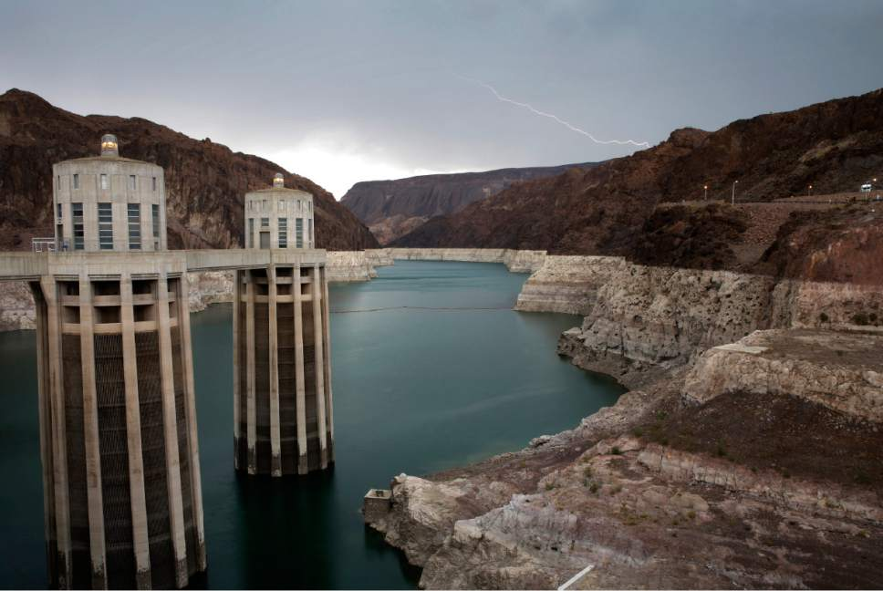 In this July 28, 2014 photo, lightning strikes over Lake Mead near Hoover Dam at the Lake Mead National Recreation Area in Arizona. Wet weather in May and June prompted optimistic projections Monday, Aug. 17, 2015 from federal water managers keeping close tabs on the Colorado River water supply for about 40 million residents in seven Southwest U.S. states. The West remains in a historic drought, and Lake Mead right now is just 38 percent full. (AP Photo/John Locher, File)