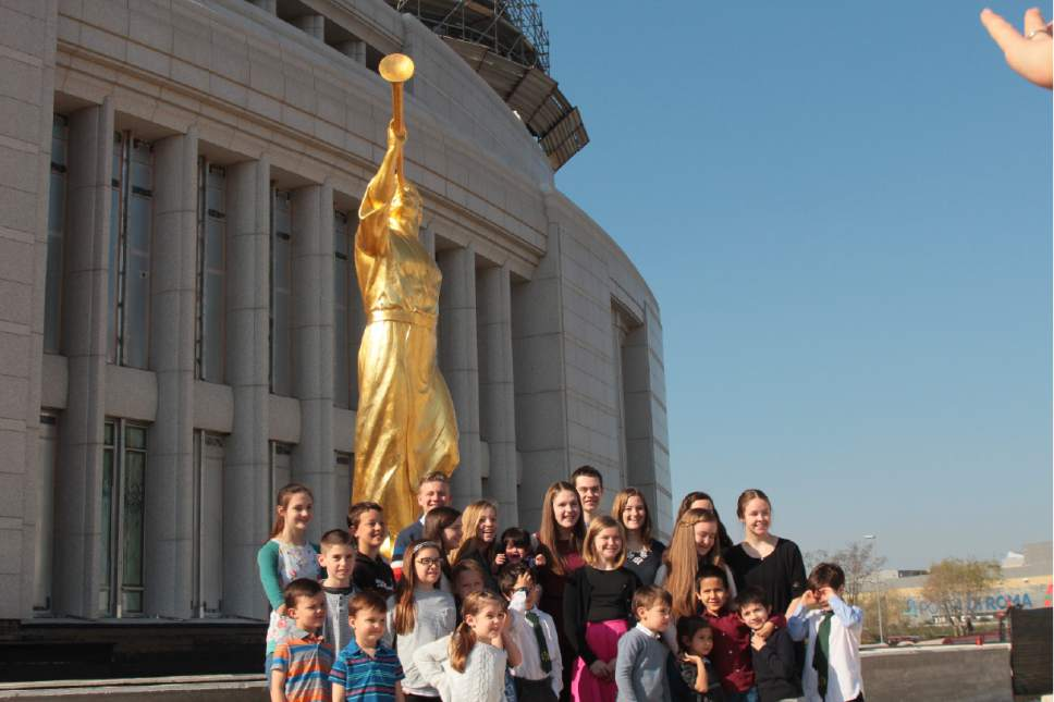 Children pose in front of the angel Moroni prior to raising the statue skyward. Courtesy Photo | Intellectual Reserve, Inc.