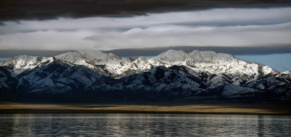 Al Hartmann  |  The Salt Lake Tribune Dark storm clouds break up over the Stansbury Mountain range seen from the Great Salt Lake Wednesday March 9.  Upper peaks are still loaded with this 2017's Winter's snowpack.