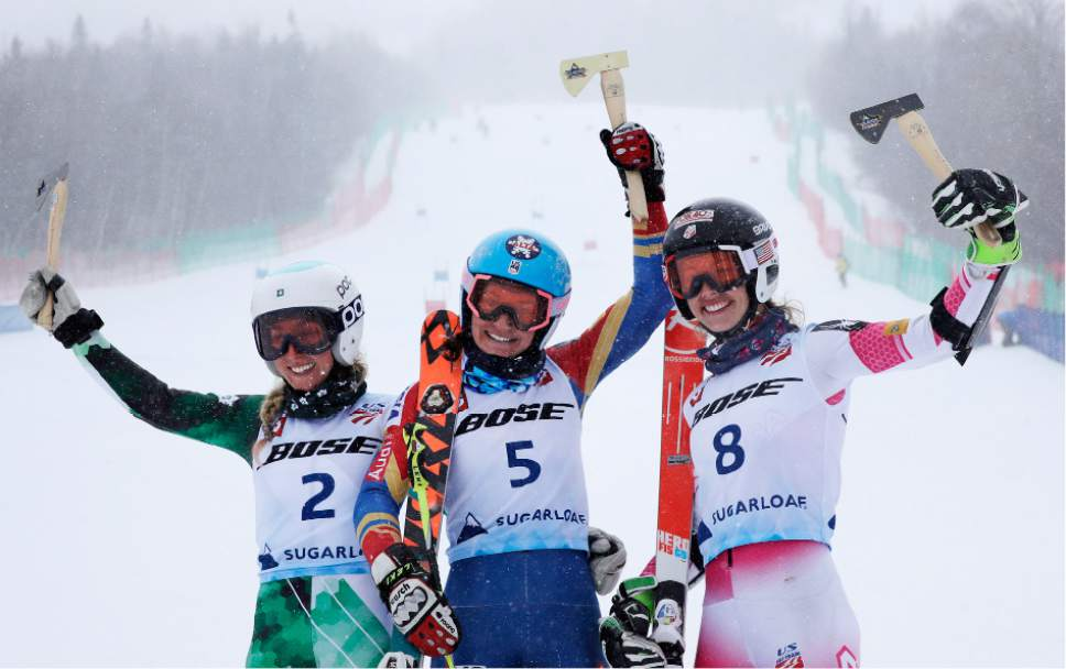 Megan McJames, of Park City, Utah, (5) raises the golden hatchet trophy after winning the women's giant slalom skiing race at the U.S. Alpine Ski Championships at Sugarloaf Mountain Resort in Carrabassett Valley, Maine, Monday, March 27, 2017. With McJames are second place finisher Foreste Peterson (2) and third place finisher Patricia Mangan (8). (AP Photo/Charles Krupa)