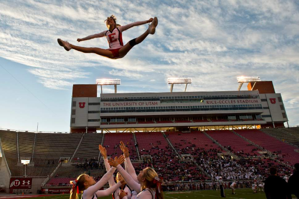 Chris Detrick  |  The Salt Lake Tribune East High senior cheerleader Sammie Tidwell completes a toe touch basket toss during the East vs Olympus football game at Rice-Eccles Stadium Thursday November 14, 2013. East won the game 47-21.