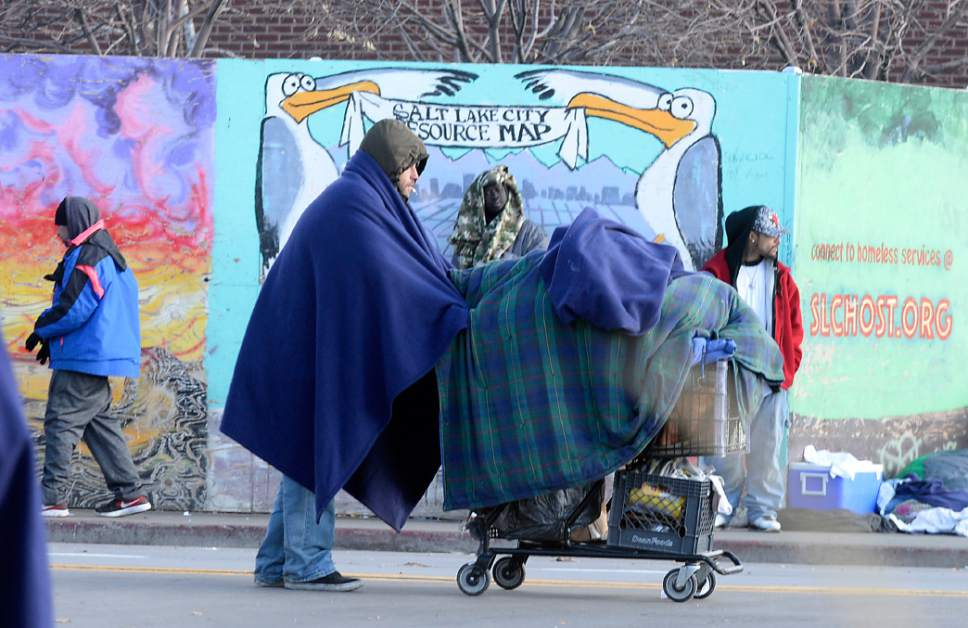 Al Hartmann  |  The Salt Lake Tribune Bundled up homeless people in blankets and winter clothing either hunker down in place or keep walking to stay warm along 500 West near the Road Home shelter on a cold morning Wedneday Dec. 7.   The Collective Impact steering committee met today to review a survey of homeless people in the Rio Grande area to determine if more overflow shelter space is needed.