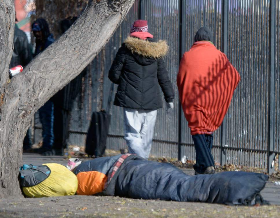 Al Hartmann  |  The Salt Lake Tribune Bundled up homeless people walk along 500 West near the Road Home shelter past a person on the sidewalk in a sleeping bag on a cold morning Wedneday Dec. 7.   The Collective Impact steering committee met today to review a survey of homeless people in the Rio Grande area to determine if more overflow shelter space is needed.