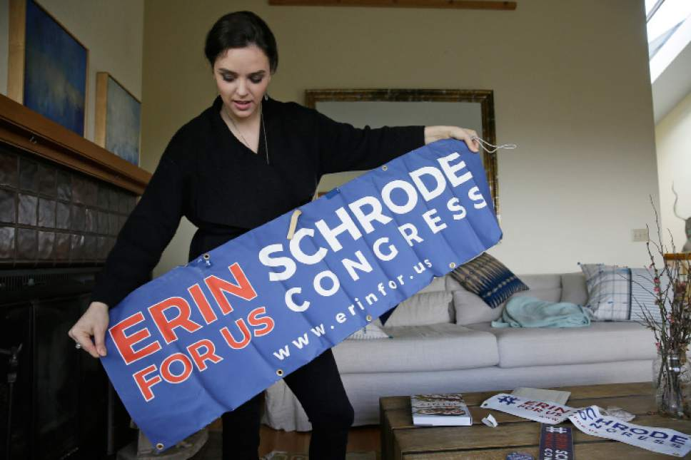In this Feb. 21, 2017, photo, Erin Schrode unfurls a campaign banner at her home in Mill Valley, Calif. Less than a week before the election for her long-shot congressional campaign, Schrode woke up in her northern California home, rolled over in bed and reflexively checked her cellphone. The 25-year-old activist burst into tears when she found a barrage of anti-Semitic emails. (AP Photo/Eric Risberg)