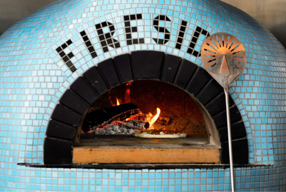 Steve Griffin  |  The Salt Lake Tribune   A pizza cooks in the Valoriani oven at Fireside on Regent in Salt Lake City on Friday, March 24, 2017. The restaurant, the first to open on the updated street, is attached to the backside of the new downtown Eccles Theater.
