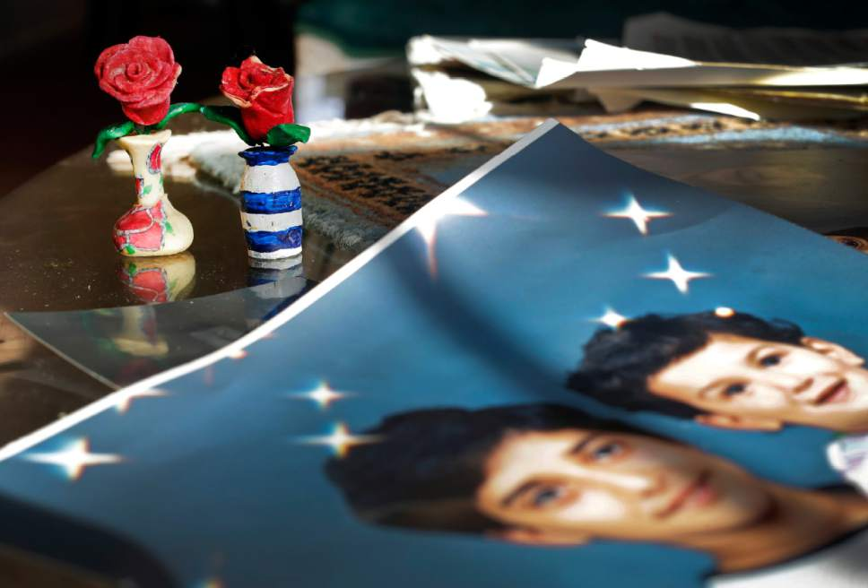 """FILE - In this  Dec. 10, 2014 file photo, prison artwork created by Adnan Syed sits near family photos in the home of his mother, Shamim Syed, in Baltimore. Adnan Syed, a convicted killer at the center of the first season of the podcast """"Serial,"""" is scheduled to appear in court Wednesday, Feb. 3, 2016 as his attorneys argue for a new trial. (AP Photo/Patrick Semansky, File)"""