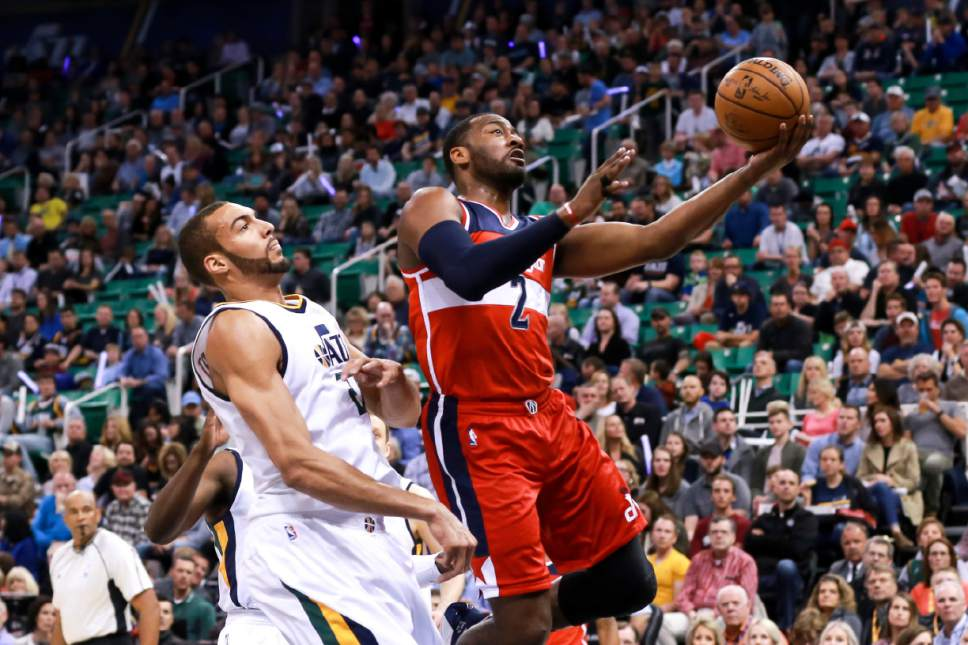 Washington Wizards guard John Wall (2) dribbles past Utah Jazz center Rudy Gobert (27) and lays the ball up to the basket during the first quarter of NBA basketball game Friday, March 31, 2017, in Salt Lake City. (AP Photo/Chris Nicoll)