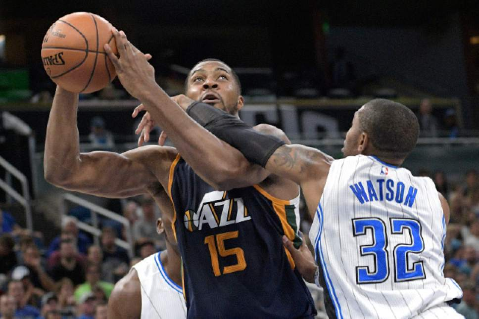 Utah Jazz forward Derrick Favors (15) is fouled while going up for a shot by Orlando Magic guard C.J. Watson (32) during the second half of an NBA basketball game in Orlando, Fla., Friday, Nov. 11, 2016. The Jazz won 87-74. (AP Photo/Phelan M. Ebenhack)