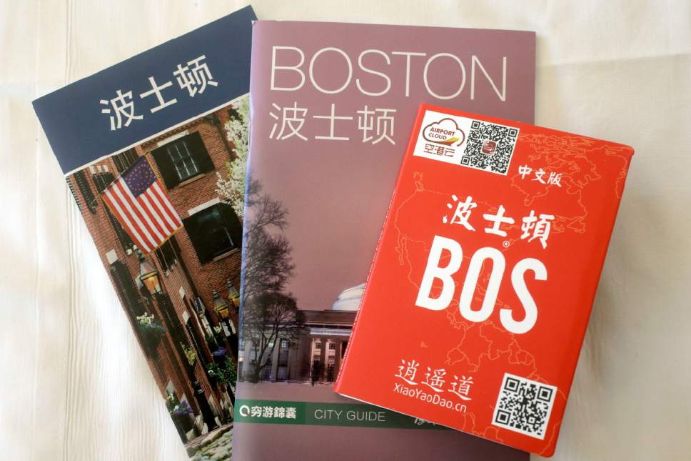 In this March 23, 2017, photo, an activities guide, left, a city guide, center, and a pop-up map, right, all with Chinese translations, are displayed in a guest room at the Sheraton Boston Hotel in Boston. The brochures are included in a welcoming kit that also contains creature comforts that many Chinese travelers expect, including an electric kettle, green tea, instant noodles, slippers, and a robe. In cities across the country, the American hospitality industry is stepping up efforts to make Chinese visitors feel more welcome. (AP Photo/Steven Senne)