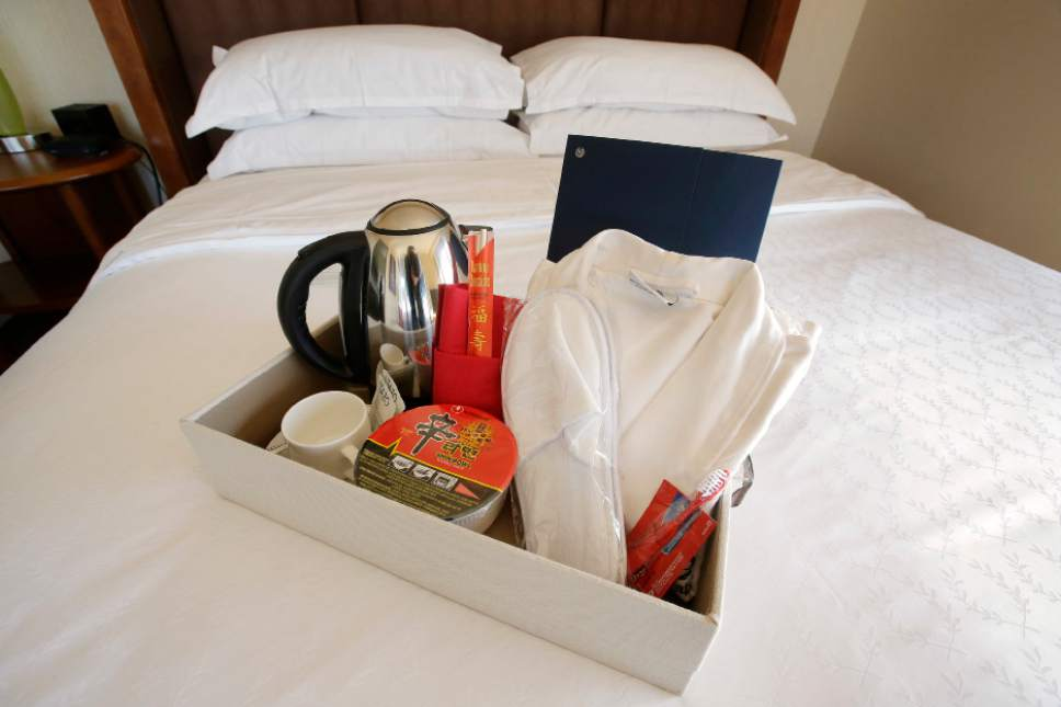 In this March 23, 2017 photo, items in a welcoming kit containing creature comforts that many Chinese travelers expect in their rooms, including, from the left, an electric kettle, green tea, instant noodles, slippers, and a robe, rest in a tray on a bed in a guest room at the Sheraton Boston Hotel in Boston. In cities across the country, the American hospitality industry is stepping up efforts to make Chinese visitors feel more welcome. (AP Photo/Steven Senne)
