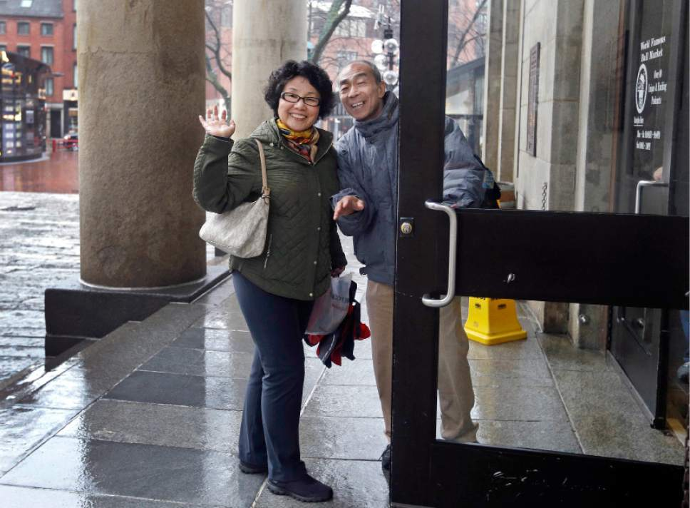 In this March 27, 2017 photo, tourists from China enter Quincy Market in Boston. In cities across the country, the American hospitality industry is stepping up efforts to make Chinese visitors feel more welcome. (AP Photo/Elise Amendola)