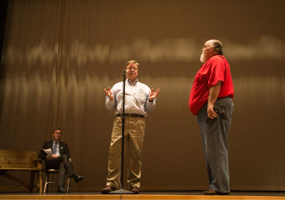 Rick Egan  |  The Salt Lake Tribune  Salt lake County Mayor Ben McAdams listens as Draper Mayor Troy Walker tries to speak over the shouts form the audience, after bring forced to the microphone to answer a question, during an open house to discuss two new potential homeless shelter sites in the Draper area, at the Draper Park Middle School auditorium, for, Wednesday, March 29, 2017.