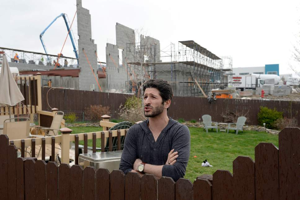 Al Hartmann  |  The Salt Lake Tribune Travis Lucero who has lived in his home on Election Road in Draper is not happy at all with American Preparatory Academy's school expansion construction in his backyard.  The build up of the ground at the project is almost as high as his existing fence.  He is planning on selling along with other neighbors along the street.   APA has been told to halt construction of its new high school campus Thursday morning but workers were still on the job in the afternoon Thursday March 30.
