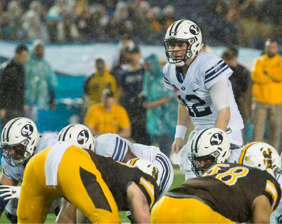 Rick Egan     The Salt Lake Tribune  Brigham Young Cougars Brigham Young Cougars quarterback Tanner Mangum (12) examine the defense, before running for a BYU touchdown, in the Poinsettia Bowl, at Qualcomm Stadium in San Diego, December 21, 2016.