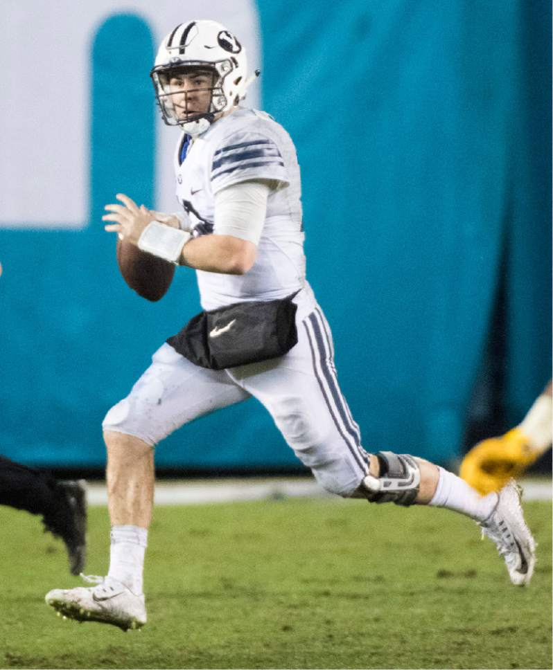 Rick Egan     The Salt Lake Tribune  Brigham Young Cougars quarterback Tanner Mangum (12) scrambles in the backfield, as BYU defeated the Wyoming Cowboys, 24-21, in the Poinsettia Bowl, at Qualcomm Stadium in San Diego, December 21, 2016.