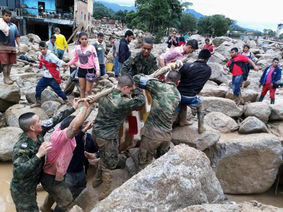 In this handout photo released by the Colombian National Army, soldiers and residents work together in rescue efforts in Mocoa, Colombia, Saturday, April 1, 2017, after an avalanche of water from an overflowing river swept through the city as people slept. The incident triggered by intense rains left at least 100 people dead in Mocoa, located near Colombia's border with Ecuador. (Colombian Army Photo via AP)