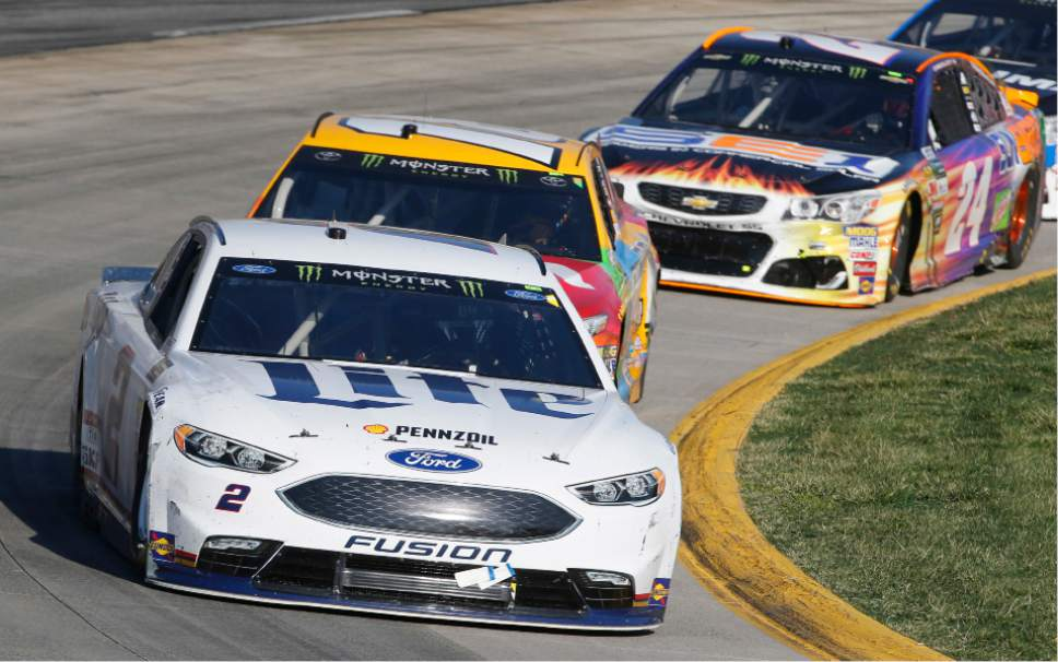 Brad Keselowski (2) leads Kyle Busch (18) in Turn 4 during the