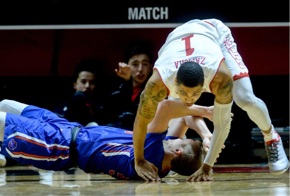 Steve Griffin  |  The Salt Lake Tribune   Utah Utes guard JoJo Zamora (1) falls on Boise State Broncos guard James Reid (55) after blocking his shot during the Utah versus Boise State basketball game in the first round of the NIT at the Huntsman Center on the University of Utah campus in Salt Lake City Tuesday March 14, 2017.