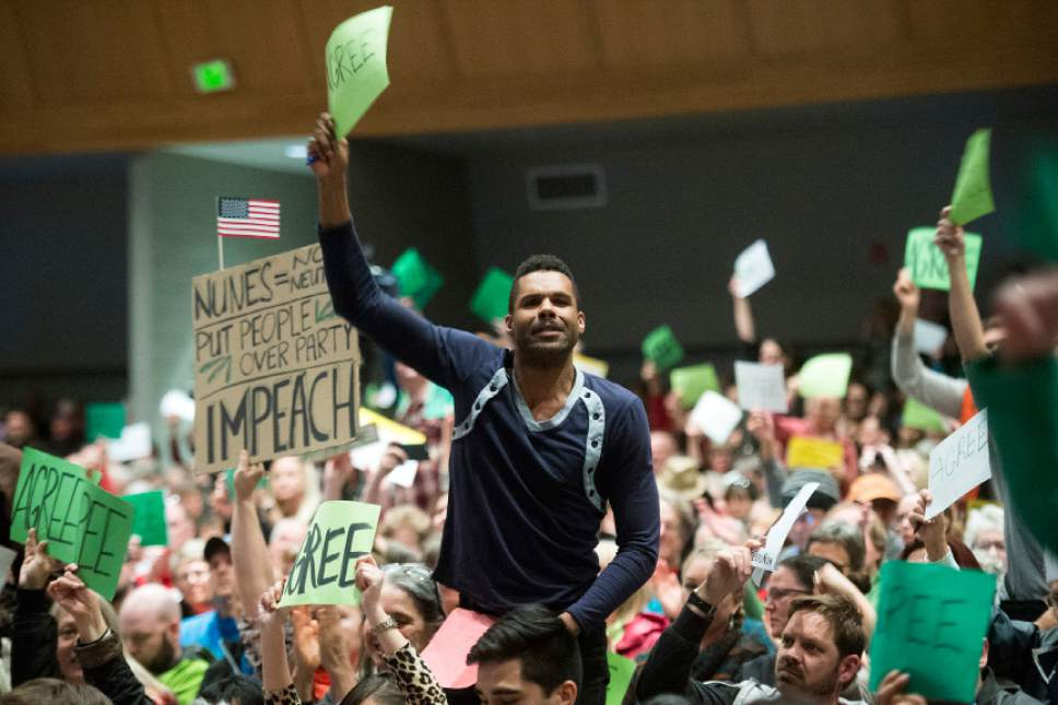 Chris Detrick  |  The Salt Lake Tribune Members of the audience hold up signs while yelling and cheering at Rep. Chris Stewart during a town hall meeting at West High School Friday March 31, 2017.