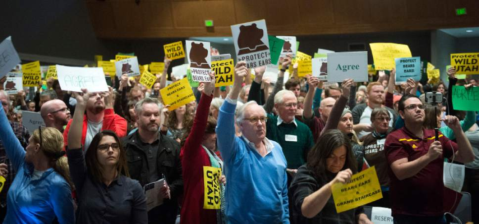 Chris Detrick  |  The Salt Lake Tribune Members of the audience hold up signs at Rep. Chris Stewart during a town hall meeting at West High School Friday March 31, 2017.