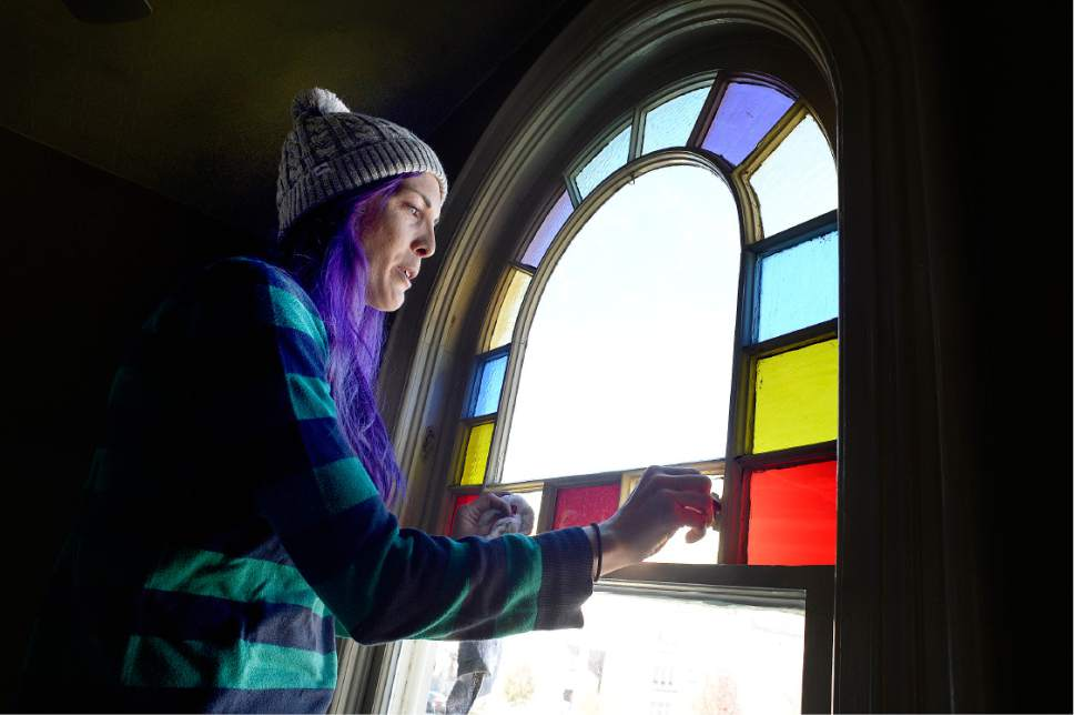 "Scott Sommerdorf   |  The Salt Lake Tribune   Jess Mikel cleans a rainbow edged window that looks out to the north with a view of the Provo LDS Temple during a work / cleanup day at the old Victorian home being renovated to house ""Encircle House"" which will be Provo's first LGBT resource center, Saturday November 19, 2016."