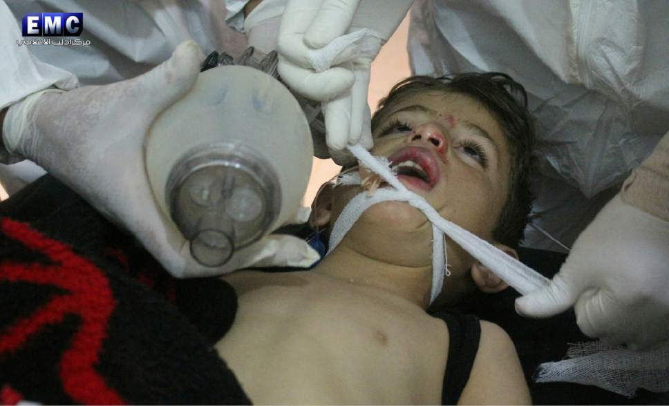 This photo provided by the Syrian anti-government activist group Edlib Media Center, which has been authenticated based on its contents and other AP reporting, shows  Syrian doctors treating a child following a suspected chemical attack, at a makeshift hospital, in the town of Khan Sheikhoun, northern Idlib province, Syria. The suspected chemical attack killed dozens of people on Tuesday, Syrian opposition activists said, describing the attack as among the worst in the country's six-year civil war. (Edlib Media Center, via AP)