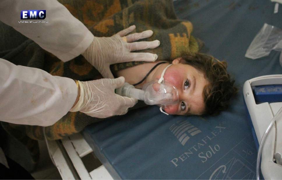 This photo provided by the Syrian anti-government activist group Edlib Media Center, which has been authenticated based on its contents and other AP reporting, shows a Syrian doctor treating a child following a suspected chemical attack, at a makeshift hospital, in the town of Khan Sheikhoun, northern Idlib province, Syria. The suspected chemical attack killed dozens of people on Tuesday, Syrian opposition activists said, describing the attack as among the worst in the country's six-year civil war. (Edlib Media Center, via AP)