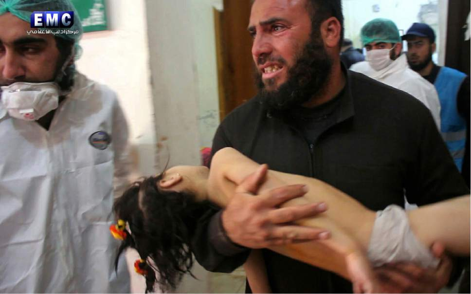 This photo provided on Tuesday April 4, 2017, by the Syrian anti-government activist group Edlib Media Center, that is consistent with independent AP reporting, shows a man carrying a child following a suspected chemical attack, at a makeshift hospital in the town of Khan Sheikhoun, northern Idlib province, Syria. The suspected chemical attack killed dozens of people on Tuesday, Syrian opposition activists said, describing the attack as among the worst in the country's six-year civil war. (Edlib Media Center, via AP)