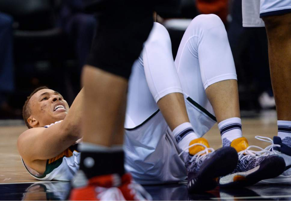 Steve Griffin     The Salt Lake Tribune   Utah Jazz guard Dante Exum (11) holds his side in pain after falling to the court while going to the basket during the Utah Jazz versus Portland Trailblazers NBA basketball game at Vivint Smart Home Arena in Salt Lake City Tuesday April 4, 2017.