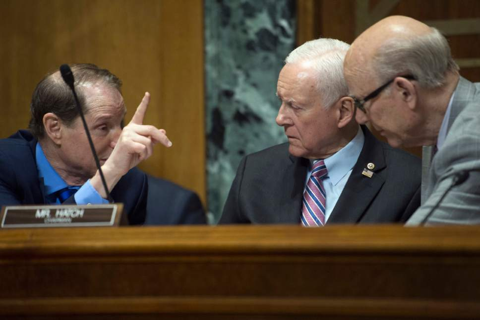Senate Finance Committee Chairman Sen. Orrin Hatch, R-Utah, center, confers with the Committee's ranking Member Sen. Ron Wyden, D-Ore.,left, and Sen. Pat Roberts, R-Kansas on Capitol Hill in Washington, Thursday, April 6, 2017, during the committee's hearing with IRS Commissioner John Koskinen. (AP Photo/Cliff Owen)