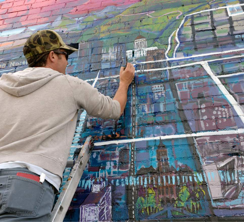 "Al Hartmann  |  The Salt Lake Tribune Artist Chris Peterson puts on finishing details of a vibrant new 54 x 20 foot mural showcasing Salt Lake Cityís bikeways at 750 South State Street Thursday April 6.  The mural is a perspectival map of Salt Lake Cityís bikeways, featuring prominent city landmarks, the downtown and Wasatch skylines and the 9-Line Trail, Jordan River Parkway Trail and Bonneville Shoreline Trail. He started the mural last fall, was  halted by winter, and should be done in the next few days.   ìThe mural is meant to provide a bicycle-oriented perspective on the Salt Lake City landscape.  Downtown bike lanes connect to trails along the river and in the foothills,"" explains Peterson. ìThis artwork is about our cityís amazing landscape the growing bike infrastructure that spans it.î  The SLC Bikeways Mural Project was made possible through support and collaboration with Crank SLC owners Christian Clemens and Juliet Lalouel, Bike Utah, and multimedia artist Patrick Clifford. The project also received support from the Utah Division of Arts and Museumsí ìRandom Acts of Artî grant program."