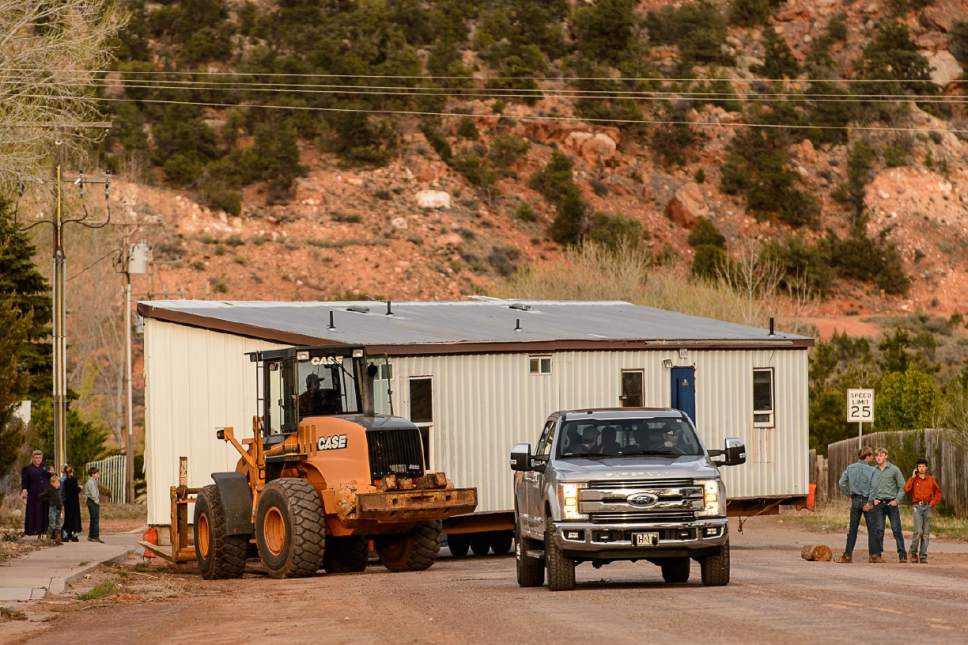 Trent Nelson  |  The Salt Lake Tribune A group of FLDS members move a modular home from a lot in Hildale as part of an eviction from UEP trust property, Wednesday April 5, 2017. Many FLDS members have refused to cooperate with the state-controlled land trust and are now facing eviction.